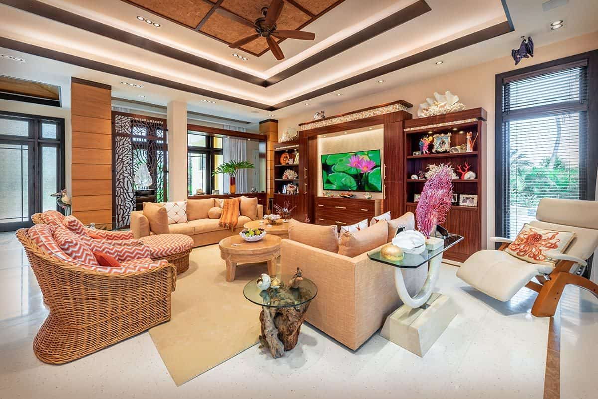 Living room interior of an energy-efficient coastal style home with tray ceiling, ceiling fan, and sandy-colored furniture and area rug on white tile flooring.