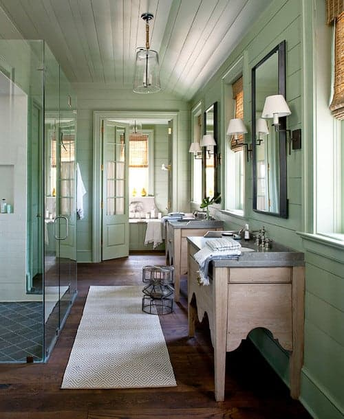 Green bathroom boasts shiplap walls and natural wood plank flooring lined with a diamond patterned runner. It is lighted by a glass pendant that hung from the vaulted ceiling.