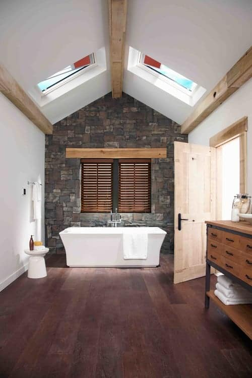 Spacious bathroom illuminated by a pair of skylights fitted on the cathedral ceiling lined with light wood beams. It has a wooden washstand and freestanding tub placed against the stone brick accent wall.