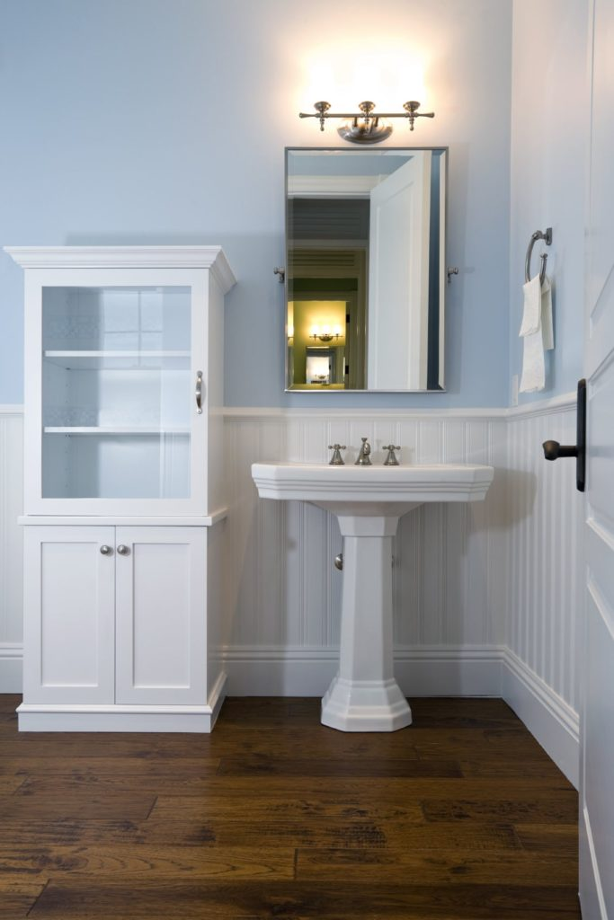 Wood plank flooring creates a warm and cozy feel in this light blue bathroom with a white storage cabinet and pedestal sink blending in with the white beadboard wall.