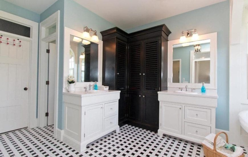 Charming bathroom with white his and her sink vanity beautifully contrasted with black louvered cabinet placed against the light blue walls. An eye-catching patterned flooring adds a striking accent to the room.