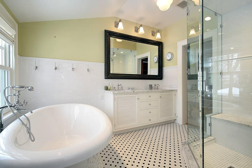 This bathroom offers a sleek bathtub and walk-in shower with a tiled bench along with a white louvered vanity topped with marble counter and dual sink.