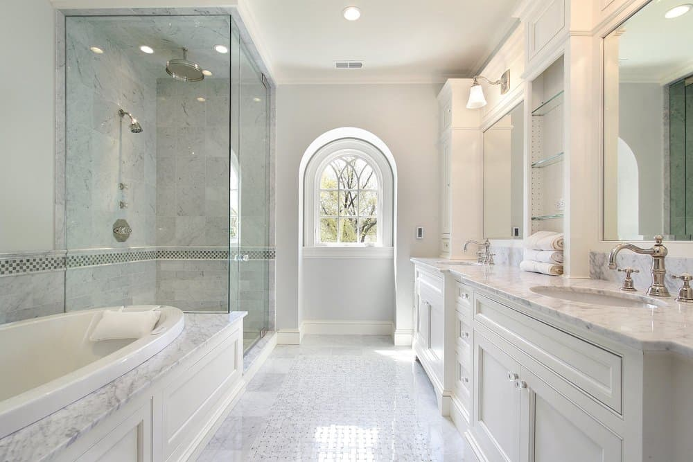 An all-white bathroom with a galley layout featuring his and her sink vanity placed across the soaking tub and walk-in shower that's enclosed in frameless glass.