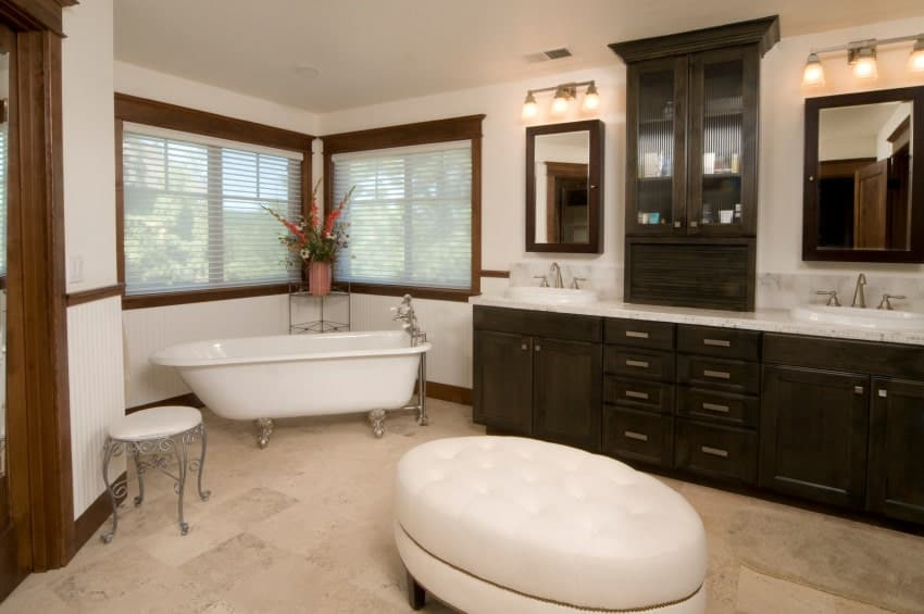 A dark wood vanity and storage cabinet add a striking contrast in this white bathroom showcasing round tufted ottoman and a clawfoot tub paired with an ornate side table.