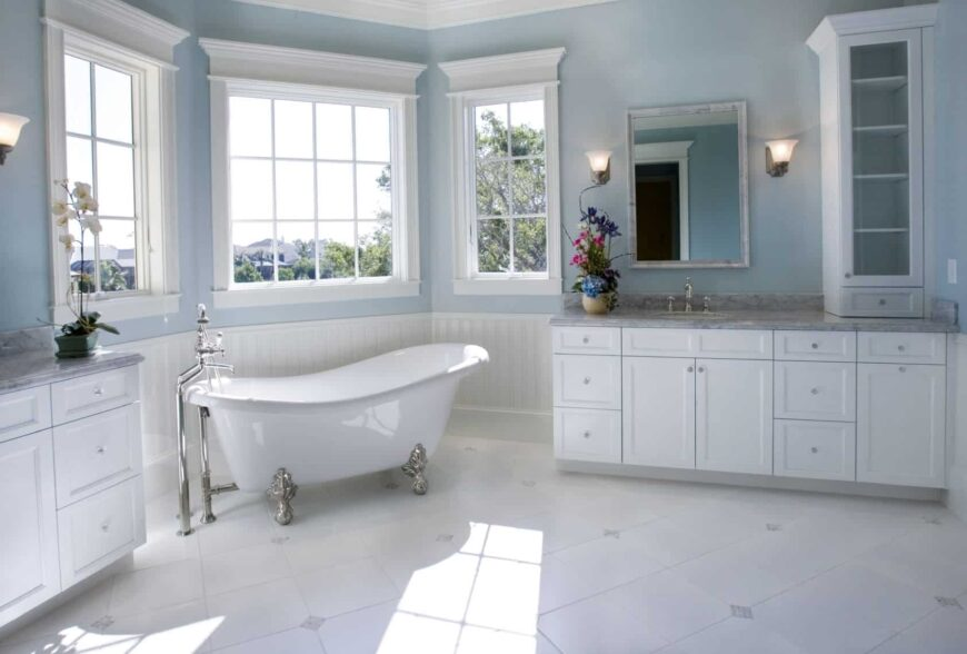 Natural light streams in through the white framed window in this sky blue bathroom with a clawfoot tub flanked by marble top sink vanities.