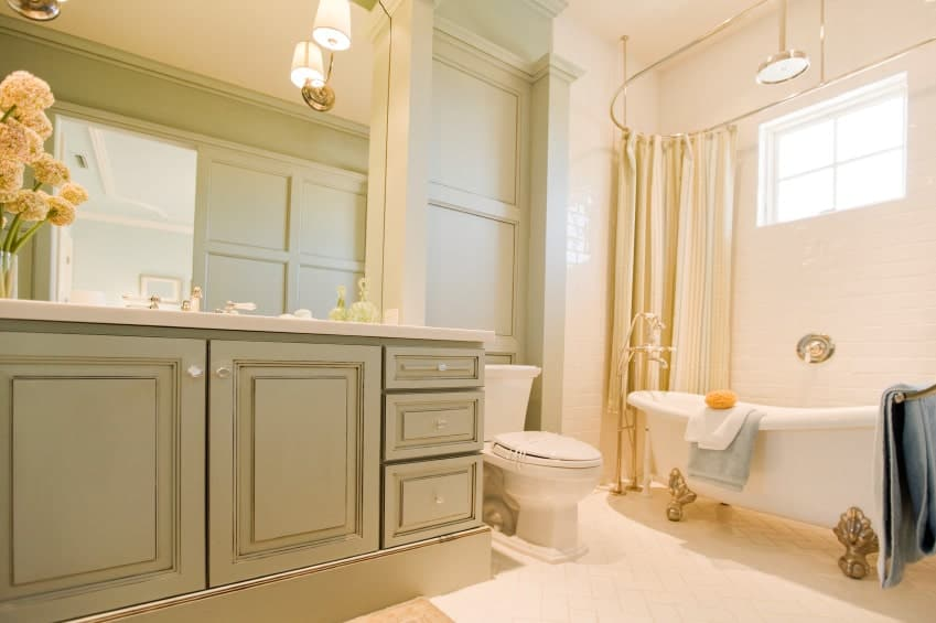 Warm bathroom offers a sage green vanity and porcelain toilet along with a tub and shower combo covered in beige curtains.