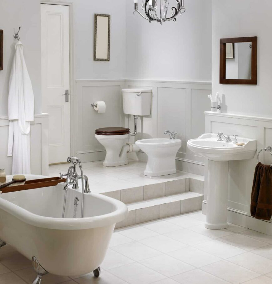 Clean, white bathroom with a pop of wood from the toilet seat, tub tray and mirror that hung over the pedestal sink. It has tiled flooring and wainscoted lower walls adding style to the plain white room.