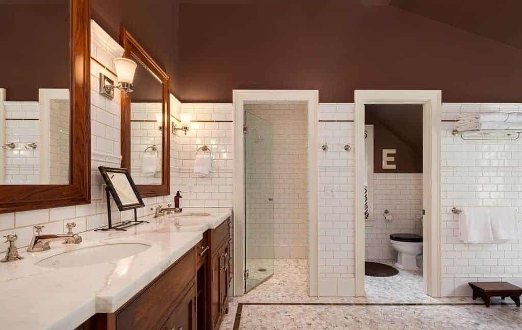 Brown bathroom clad in white brick tiles showcases a shower and toilet area along with a wooden vanity fitted with dual sink and chrome fixtures.
