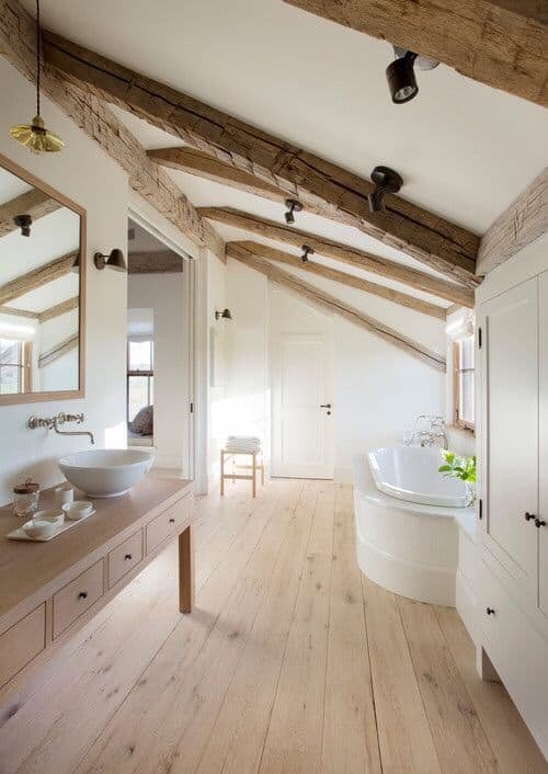 Cozy bathroom with natural wood plank flooring complementing with the washstand and shed ceiling mounted with rustic wood beams and black track lights.