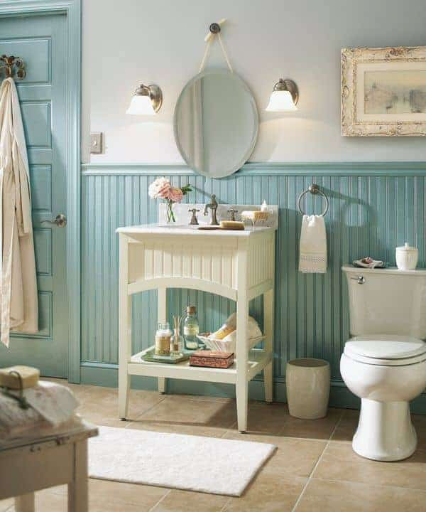 Farmhouse bathroom with blue beadboard lower wall and marble tile flooring topped by a white runner. It offers a toilet and washstand paired with an oval-shaped mirror that's flanked by glass sconces.