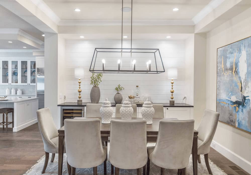 White dining room decorated with lovely artwork and stylish table lamps that sit on the built-in storage with wine fridge placed against the white shiplap wall.