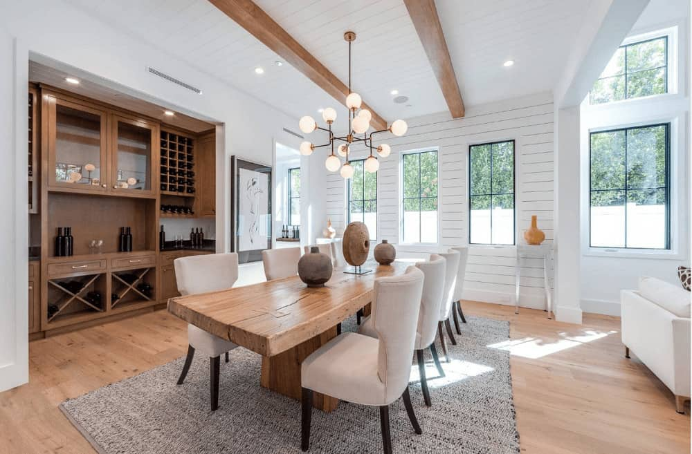 An open dining area illuminated by a glass globe chandelier that hung over the wooden dining table paired with beige wingback chairs. It has wide plank flooring and shiplap ceiling lined with wood beams.