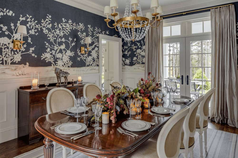 Clad in deep blue floral wallpaper and white wainscoting, this dining room offers round back chairs and a wooden dining table lighted by a gorgeous brass chandelier.