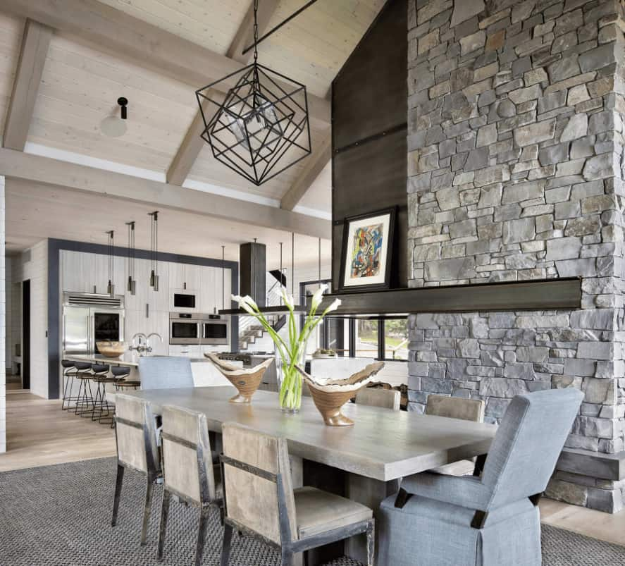 Stone brick wall adds texture in this farmhouse dining room boasting a geometric pendant light and natural wood dining set topped with decorative bowls and glass flower vase.