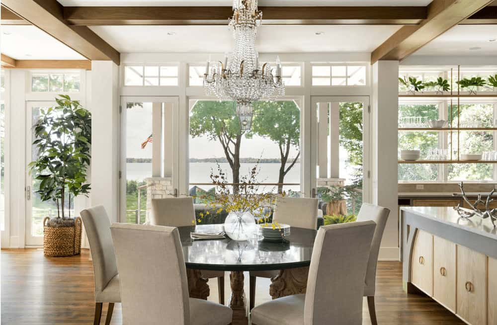 Airy dining room with hardwood flooring and glazed windows overlooking the amazing outdoor scenery. It includes round dining set and a fabulous crystal chandelier that hung from the beamed ceiling.