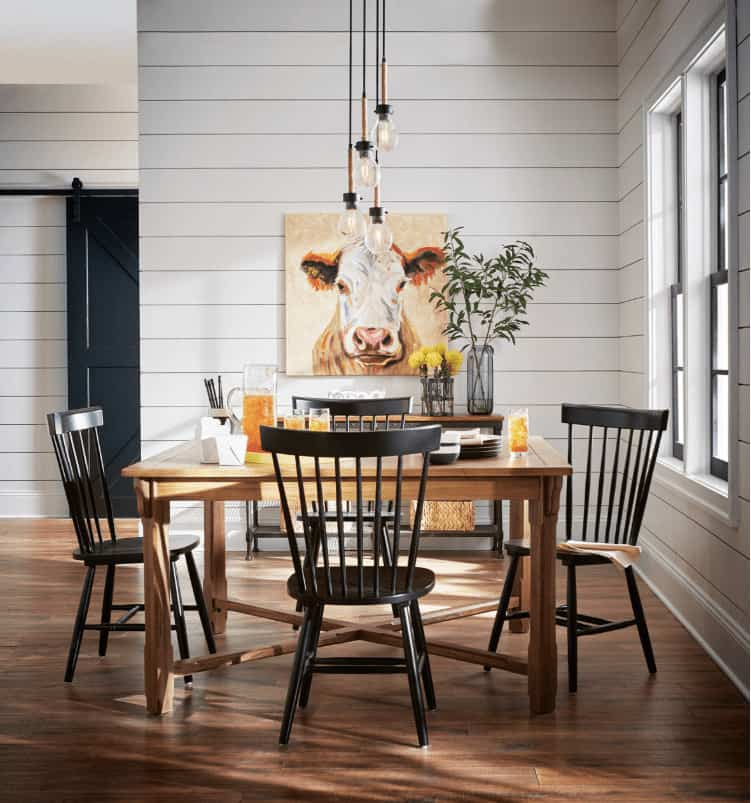 Farmhouse dining room with bulb pendant lights and a square dining table surrounded by black chairs. It has hardwood flooring and white shiplap walls accented with a stunning cow painting.