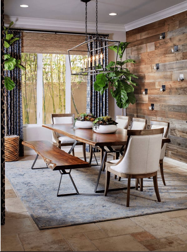 Fiddle leaf fig plants create a tropical feel in this dining room offering a wooden dining set lighted by an industrial chandelier. It has wood paneled wall and limestone flooring topped by a distressed blue rug.