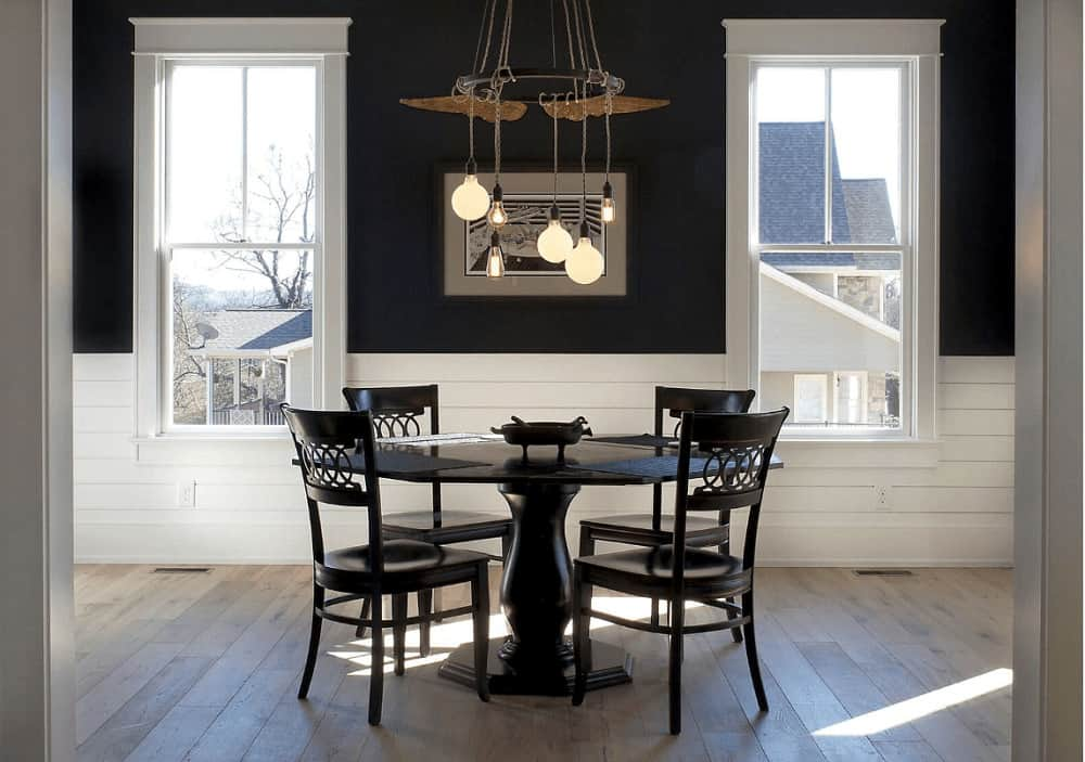 Black dining room contrasted with shiplap lower walls and white framed windows inviting natural light in. It is decorated with a lovely artwork and bulb pendants that hung over the round dining table.