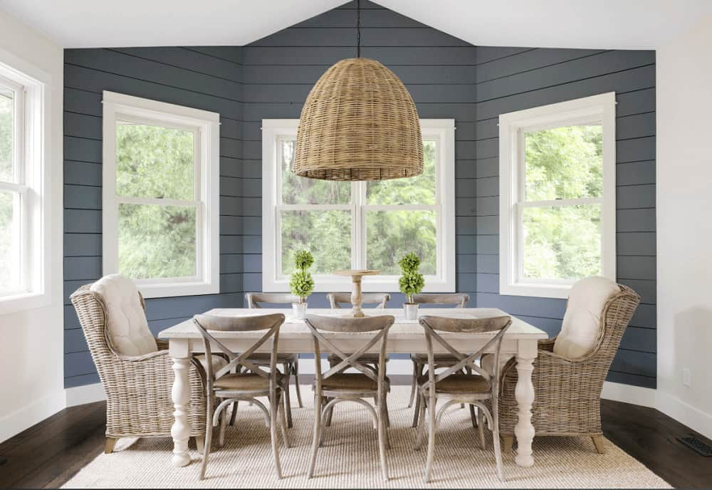Rattan wingback chairs complement the wicker dome pendant in this farmhouse dining room with a rustic dining set and white framed windows highlighted by grayish blue shiplap wall.