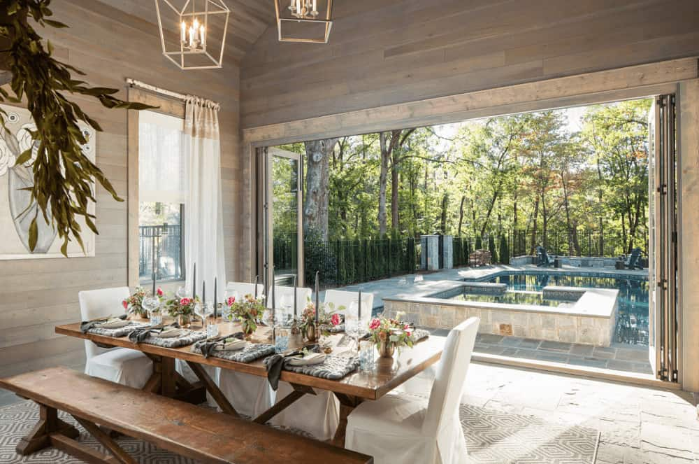 Fresh dining room with wood paneled walls and folding doors that open to the sparkling swimming pool enclosed in wrought iron fence. It has caged pendants and a wooden dining table accompanied by a matching bench and white skirted chairs.