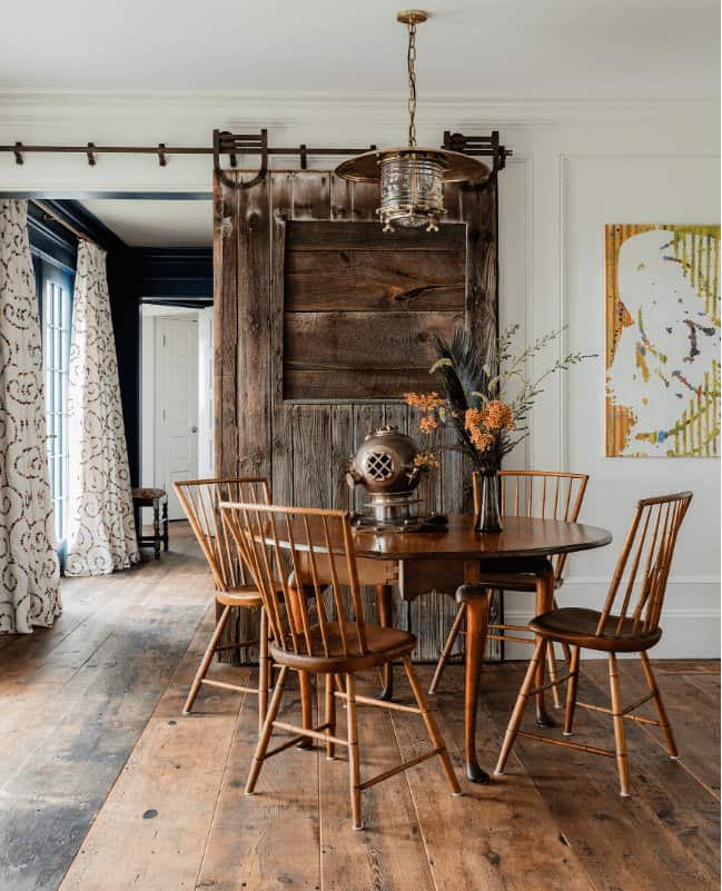 Cozy dining room showcases a rustic sliding door along with a brass pendant light and round dining set over wide plank flooring.