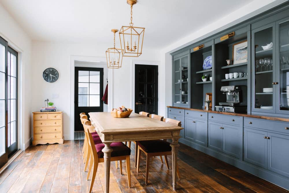 A grayish blue built-in cabinet is situated on the white inset wall in this dining room with brass pendant lights and a smooth dining table paired with wooden chairs that are fitted with burgundy cushions.