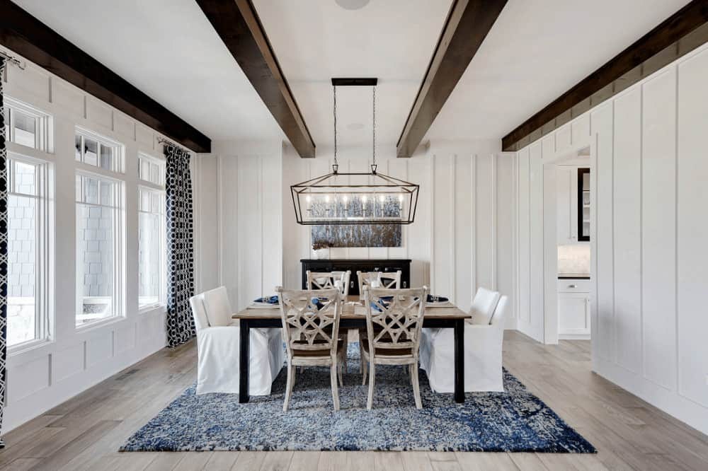 Dark wood beams add a striking contrast in this white dining room featuring a cozy dining set on a gorgeous blue rug complementing with the artwork mounted on the beadboard wall.