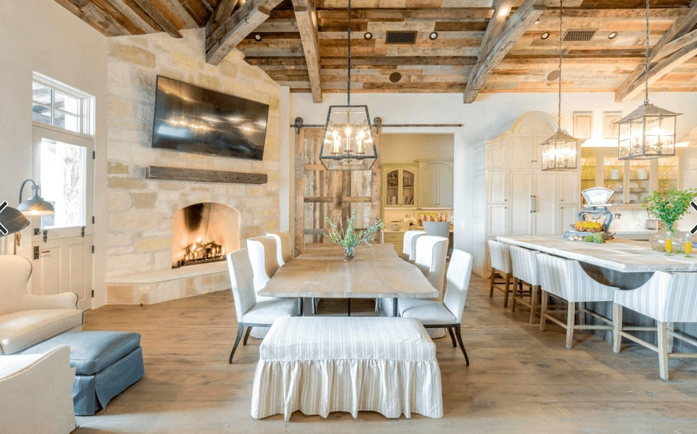 An open dining area near the stone fireplace featuring skirted bench and white wingback chairs along with a wooden dining table illuminated by a lantern pendant that hung from the wood beam ceiling.