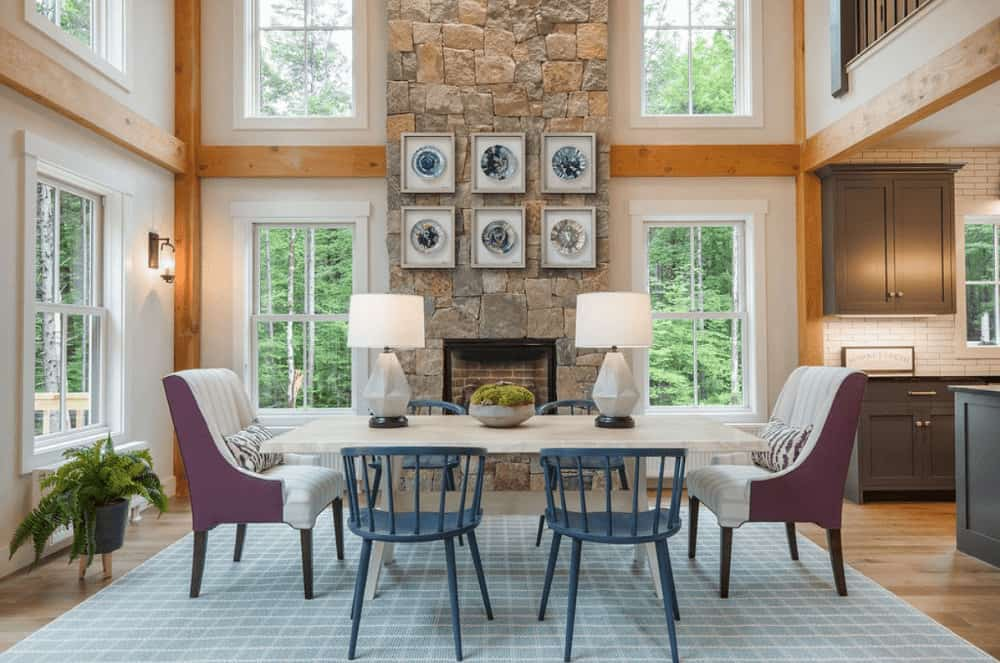 A pair of white table lamps sit on the light wood dining table surrounded by blue and striped upholstered chairs over a blue checkered rug. There's a fireplace in the middle that's fixed on the stone pillar mounted with gallery frames.