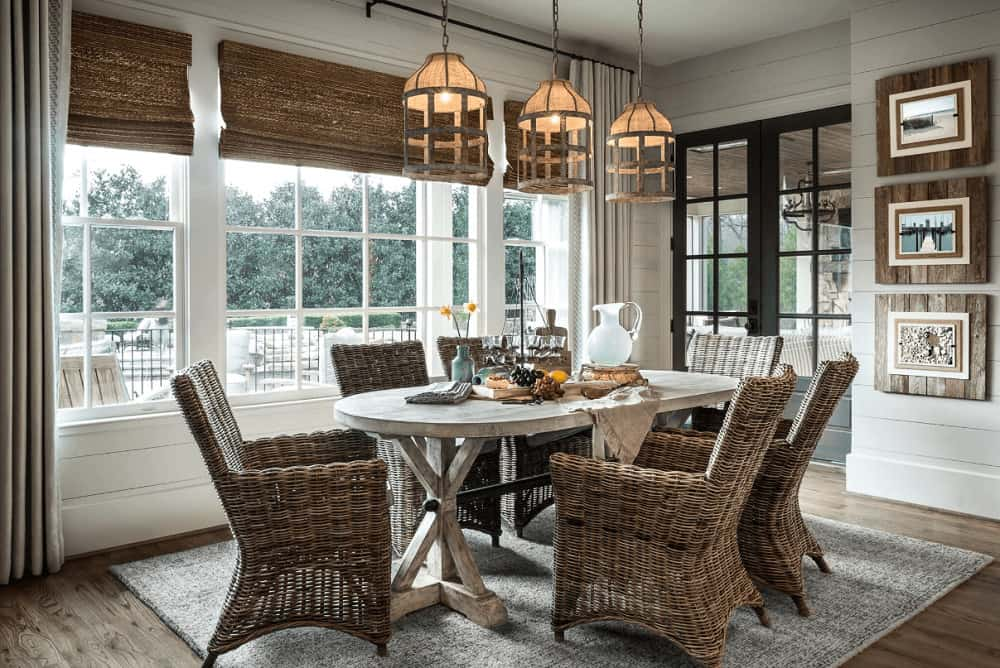 Farmhouse dining room with caged pendants and wicker chairs complementing the roman shades and framed photos mounted on the shiplap wall.
