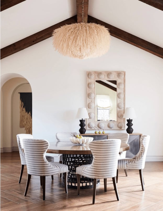 This dining room showcases a round dining set and a console table topped with black table lamps and a stylish mirror. It is illuminated by a wicker pendant that hung from the cathedral ceiling.