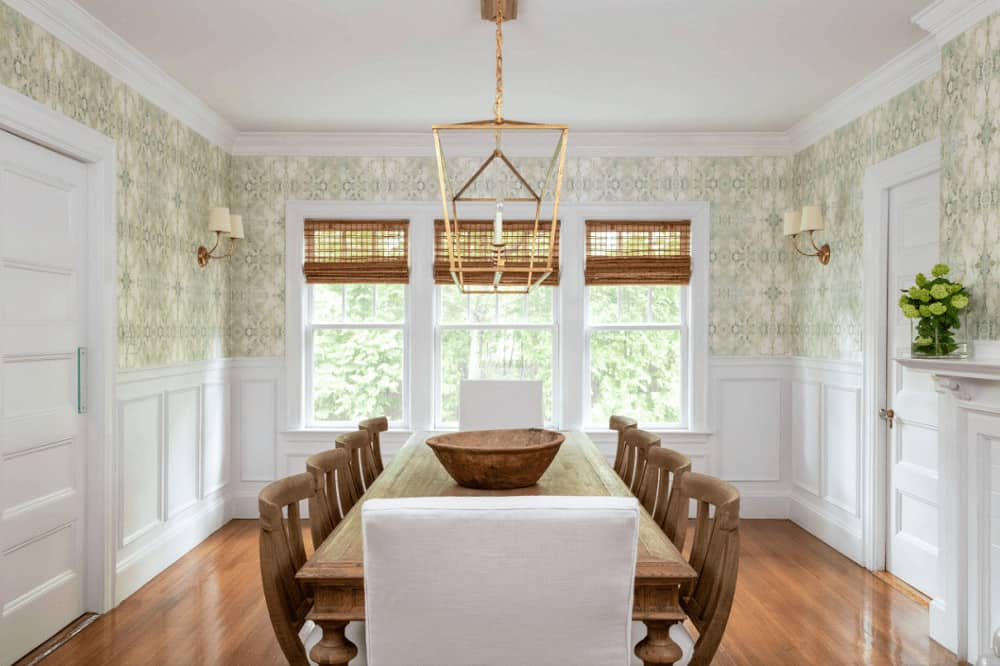 Formal dining room with rich hardwood flooring and white framed windows covered in wicker roman shades. It has a nice wallpaper and brass pendant light that hung over the wooden dining set.