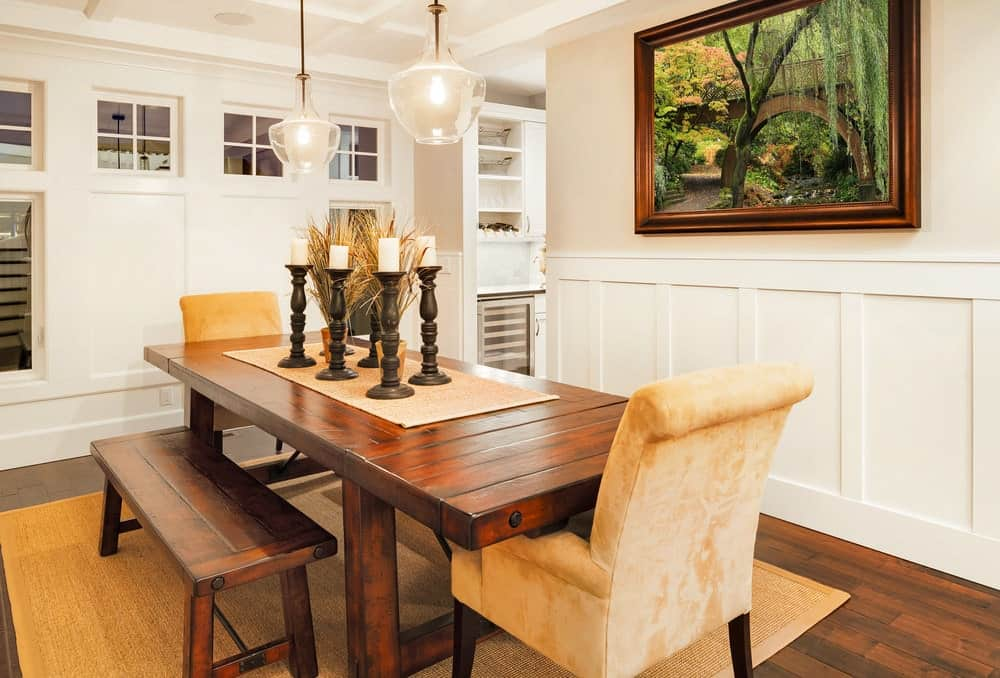 A pair of glass pendant lights illuminate this dining room offering a cozy dining set topped with black candle holders. It has a jute rug and framed landscape mounted above the white wainscoting.