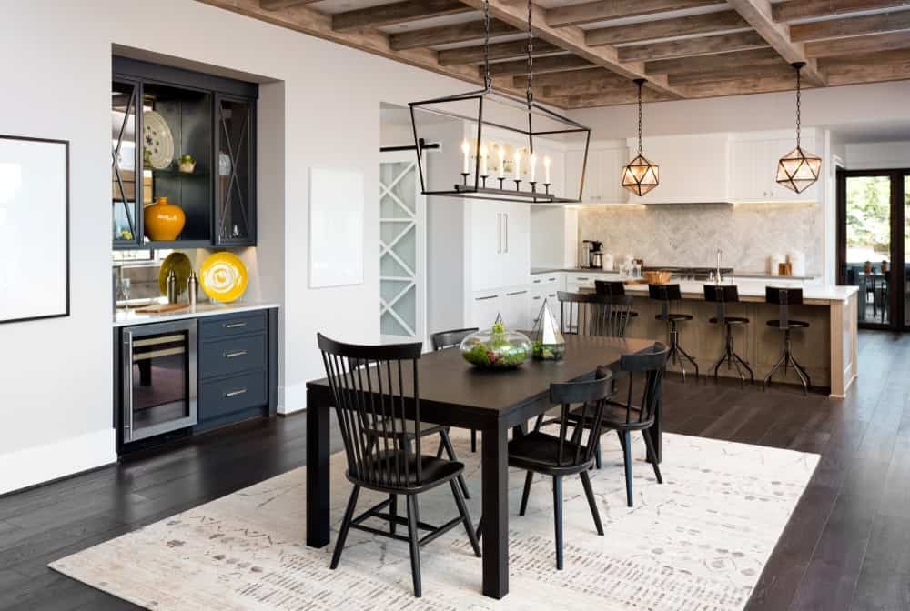 An open dining area illuminated by an industrial chandelier that hung from the wood beam ceiling. It has a black dining set that sits on a white rug over wide plank flooring.