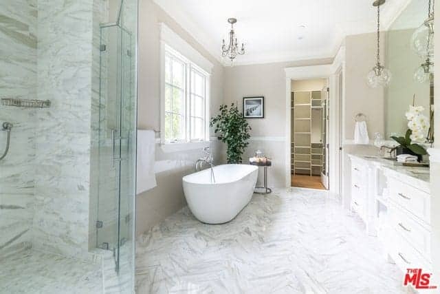 This Farmhouse-style primary bathroom has white marble flooring that extends to the walls of the glass enclosed shower area. Beside this is the freestanding bathtub brightened by the window and topped with a charming chandelier.