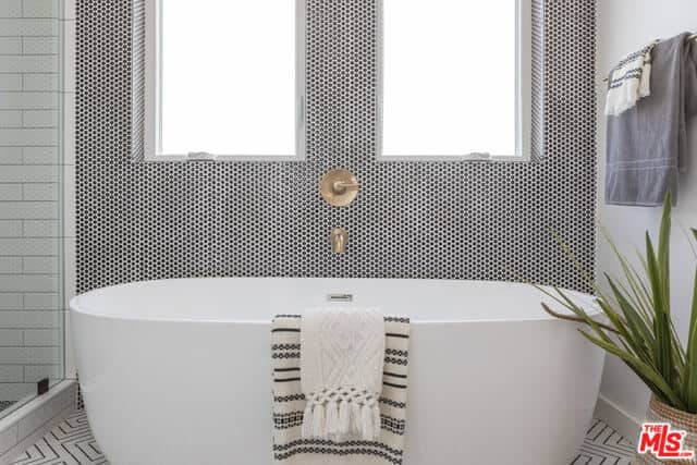 The white freestanding bathtub stands out against the wall that has a complex pattern to it contrasted by the golden faucet in between of the two windows that bring in an abundance of natural lighting to the white patterned flooring and potted plant.