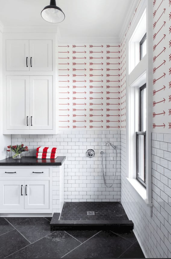 This simple bathroom has black flooring tiles that extend to the corner of the shower area beside the white cabinet with a matching black countertop. This is adorned with white wainscoting that has white tiles arranged in a brick wall pattern. Above it is a wallpaper with arrow patterns.