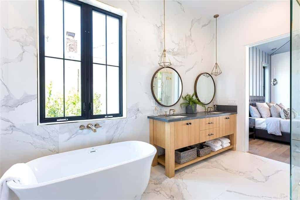 The white marble flooring tiles extends to the walls and backsplash of the white freestanding bathtub and the two-sink vanity that has cabinets, drawers and a shelf at the bottom for the towels and baskets. This is paired with round mirrors and pendant lights.