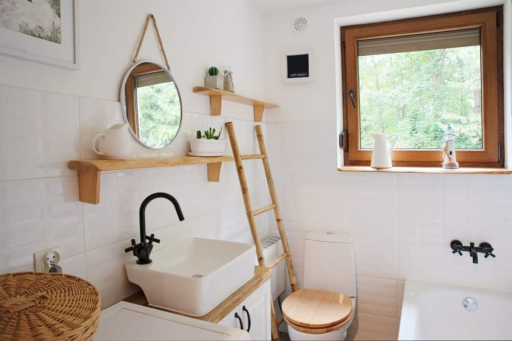 This is a small and simple Farmhouse-style bathroom that has a white porcelain toilet that has a wooden cover matching with the wooden hues of the ladder beside it, vanity countertop, shelves and the frames of the window above the head of the bathtub.