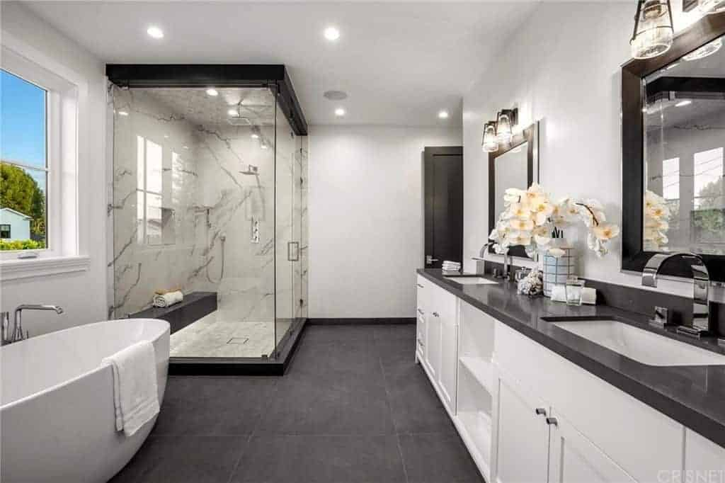 The dark gray countertop of this primary bathroom matches with the dark gray tiles of the flooring. This is then contrasted by the white freestanding bathtub and the white wooden vanity that has shaker cabinets and drawers topped with vanity mirrors.