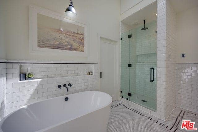 There is a beautiful colorful painting mounted on the beige upper wall by the freestanding white bathtub with a white-tiled backsplash contrasted by the black faucet. This matches with the fixtures of the shower area that has a glass door.
