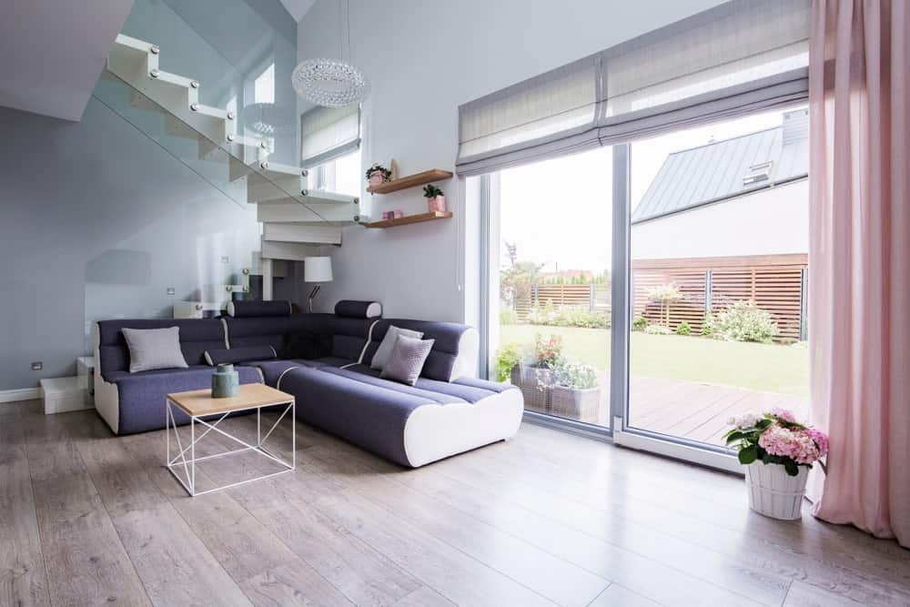 Modern living room with flat Roman shades hanging on glass sliding doors.