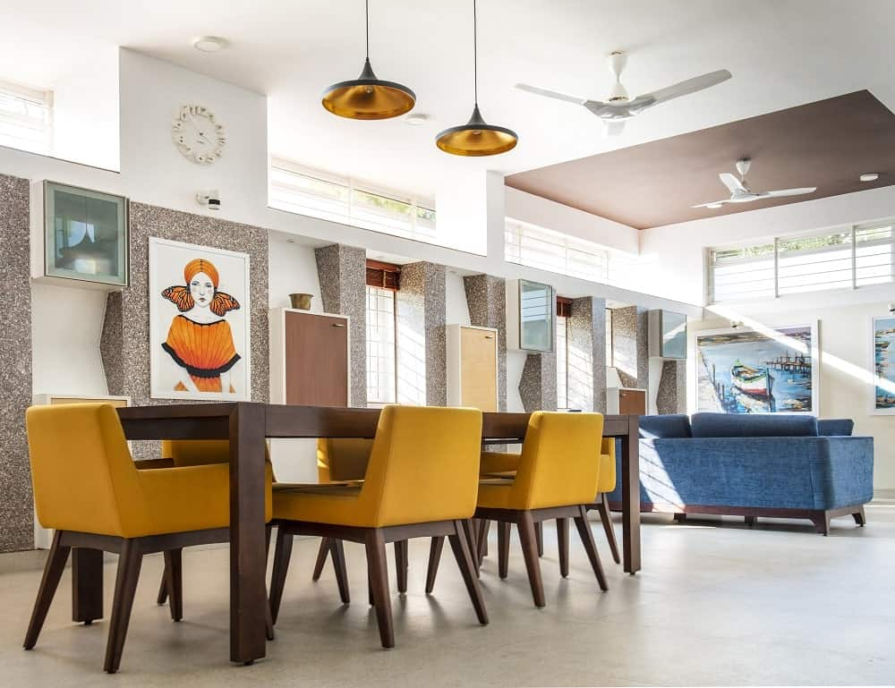 This is a close look at the dining area just a few steps from the living room area. It has a rectangular wooden dining table surrounded by yellow cushioned chairs to match the pendant lights and the wall-mounted artwork on the side.