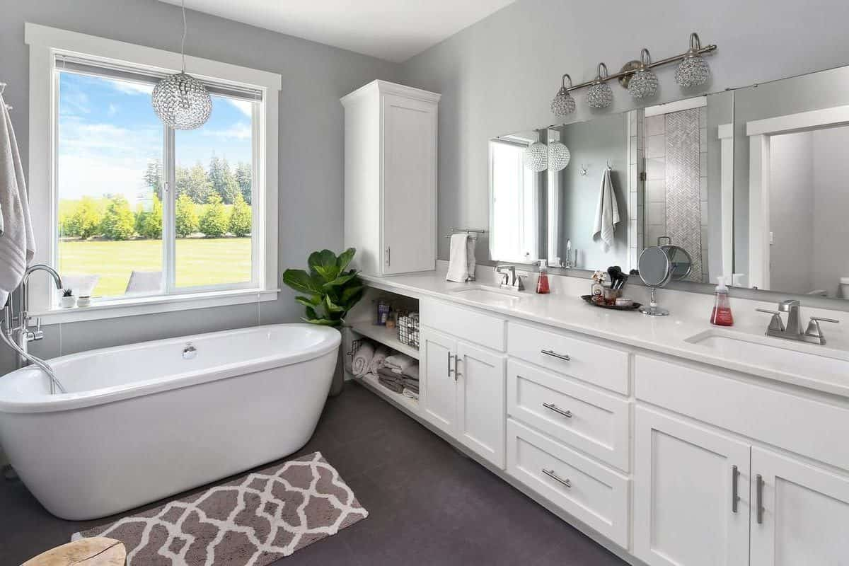 This spacious primary bathroom has a dark hardwood flooring that contrasts the white freestanding bathtub as well as the white cabinets and drawers of the two-sink vanity.
