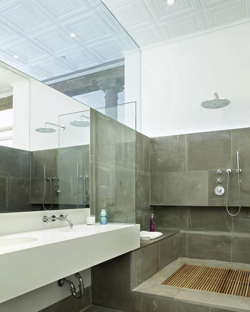 The shower area beside the white floating two-sink vanity has bare concrete walls and flooring with wooden slat-like grills for water drainage beneath the overhead shower that matches the stainless steel fixtures of the vanity.