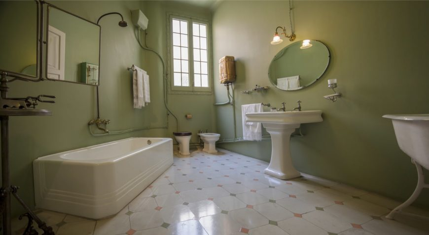 The simple white flooring tiles matches with the white bathtub, toilet and pedestal sink that contrasts the avocado green walls that are accented with the exposed pipes of the bathroom fixtures as well as the wires of the wall lamp above the mirror.