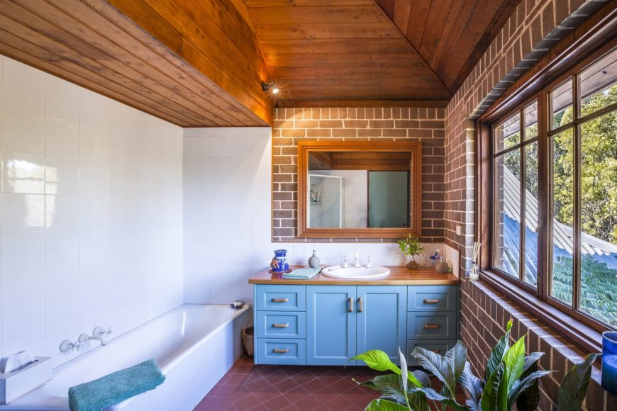 This charming bathroom has an irregular wooden arched ceiling that pairs well with the red brick walls of the vanity area side of the bathroom that has a blue vanity contrasting the terracotta flooring by the white bathtub paired with white walls.