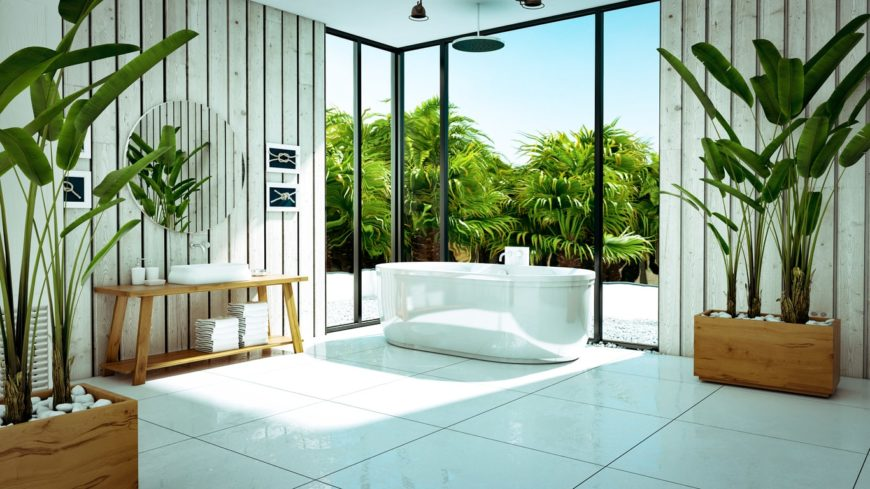 The white freestanding bathtub and its glass walls are flanked by a couple of plank shiplap walls that goes well with the wooden pot of the tropical plants as well as the wooden table supporting the white sink topped with a round mirror.