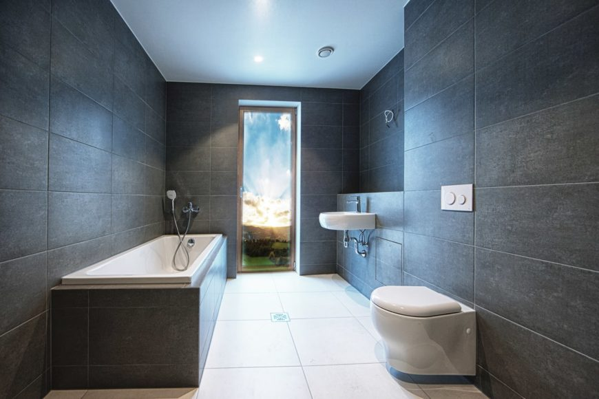 This is a simple and minimalist bathroom that has rough matte black tiles on its walls that makes the white porcelain floating sink and toilet bowl stand out as well as the white bathtub. This is complemented by the white ceiling and flooring.