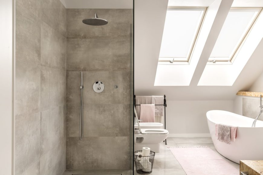 The white shed ceiling has a couple of skylights that illuminate the gray marble flooring that matches well with the concrete walls of the shower area as well as that beside the freestanding bathtub.